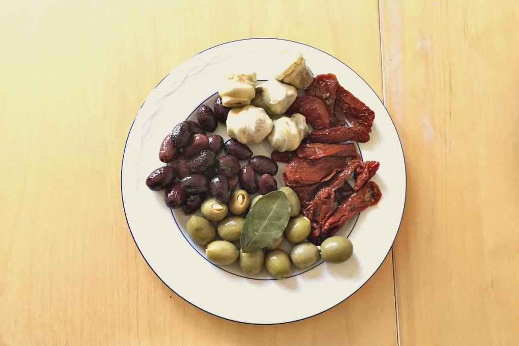 Raclette Antipasti mit grünen und schwarzen Oliven, Artischocken und getrockneten Tomaten